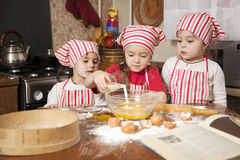 Drei kleine Chefs die Küche Lizenzfreie Stockfotos