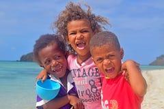 Drei kleine Fijiankinder von Yasawa-Inseln lächelnd mit vieler Aufregung deutlich sichtbar von ihrem offenen Schrei der Freude lizenzfreie stockfotografie