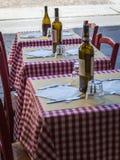 Drei kleine Holztische eingestellt mit Rot überprüfter Tischdecke, Wein-Flaschen und Tischbesteck stockfoto