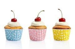Drei kleine Kuchen und Kirschen Lizenzfreie Stockbilder