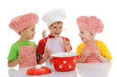 Drei kleine lustige Chefs, die Suppe zubereiten Lizenzfreies Stockfoto