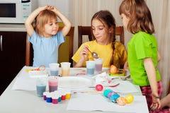 Drei kleine Mädchen, die auf Ostereiern malen stockfoto