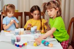 Drei kleine Mädchen, die auf Ostereiern malen Lizenzfreie Stockfotografie