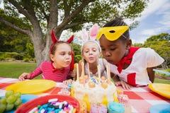 Drei kleine Mädchen, die zusammen Geburtstagskerzen durchbrennen Lizenzfreie Stockfotos