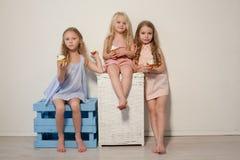 Drei kleine Mädchen essen süßen kleinen Kuchen des Kuchens mit Sahne lizenzfreie stockbilder