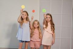Drei kleine Mädchen essen süßen Süßigkeitslutscher stockfotos