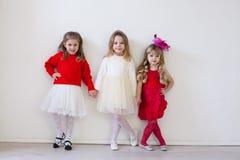 Drei kleine schöne Mädchen in den roten Griffhänden lizenzfreie stockfotografie