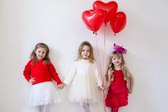 Drei kleine schöne Mädchen in den roten Griffhänden stockfoto