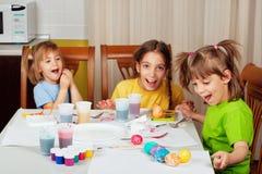 Drei kleine Schwestern, die Ostereier malen Stockfoto