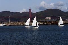 Drei kleine Segelboote, die mit Golden gate bridge in Backgro segeln Stockfotografie