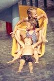 Drei Kleinkinder, die im Swimmingpool auf dem Dia spielen Stockbild