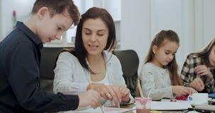 Drei Kleinkinder nach der Schule, die Hausarbeit im Wohnzimmer auf einer großen Tabelle zusammen mit ihrem reifen tuend und stock footage