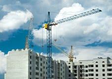 Drei Kräne, die ein Haus aufbauen Stockfotografie
