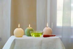 Drei kugelförmige Kerzen und Massageöl auf dem Tisch lizenzfreie stockbilder