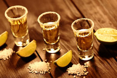 Drei kurze Gläser mit Alkohol nahe bei einer Scheibe des Kalkes und des Salzes sind auf einer alten rustikalen Tabelle mit Weinle Lizenzfreie Stockfotografie