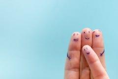 Drei lächelnde Finger, die sehr glücklich sind, Freunde zu sein Freundschaftsteamwork-Konzept auf blauem Hintergrund mit Kopienra Lizenzfreie Stockfotos