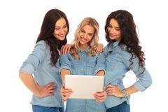 Drei lächelnde Frauen, die den Schirm einer Tablette betrachten Lizenzfreie Stockfotografie