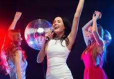 Drei lächelnde Frauen, die Karaoke tanzen und singen Lizenzfreie Stockbilder