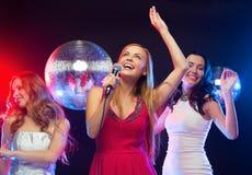 Drei lächelnde Frauen, die Karaoke tanzen und singen Lizenzfreies Stockbild