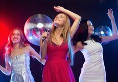 Drei lächelnde Frauen, die Karaoke tanzen und singen Stockbild