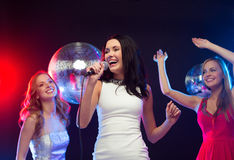 Drei lächelnde Frauen, die Karaoke tanzen und singen Stockfoto