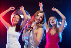 Drei lächelnde Frauen, die Karaoke tanzen und singen Stockbilder