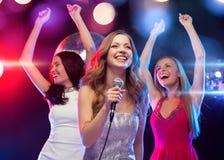 Drei lächelnde Frauen, die Karaoke tanzen und singen Lizenzfreies Stockfoto