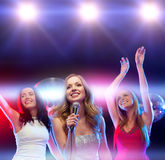 Drei lächelnde Frauen, die Karaoke tanzen und singen Stockfotos