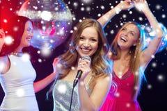 Drei lächelnde Frauen, die Karaoke tanzen und singen Lizenzfreie Stockfotos