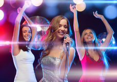 Drei lächelnde Frauen, die Karaoke tanzen und singen Lizenzfreie Stockfotografie