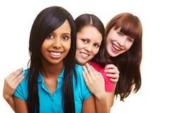 Drei lächelnde Frauen in einer Reihe stockfotografie