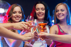 Drei lächelnde Frauen mit Cocktails und Discoball Stockfotos