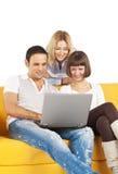 Drei lächelnde Freunde mit Laptop-Computer Stockbilder