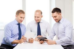 Drei lächelnde Geschäftsmänner mit Tabletten-PC im Büro Stockbild