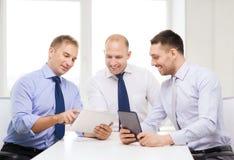 Drei lächelnde Geschäftsmänner mit Tabletten-PC im Büro Lizenzfreie Stockbilder
