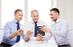 Drei lächelnde Geschäftsmänner mit Tabletten-PC im Büro Stockfotografie
