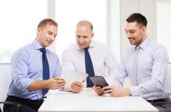 Drei lächelnde Geschäftsmänner mit Tabletten-PC im Büro Stockfotos