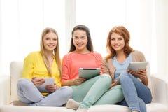 Drei lächelnde Jugendlichen mit Tabletten-PC zu Hause Lizenzfreie Stockfotos
