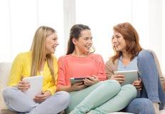 Drei lächelnde Jugendlichen mit Tabletten-PC zu Hause Lizenzfreie Stockbilder
