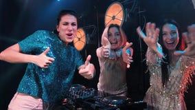 Drei lächelnde junge Mädchen versehen das Spielen von Musik auf Drehscheiben und den Gesang von Liedern mit einem Band DJ mit Dre stock footage
