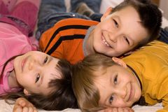 Drei lächelnde Kinder, die Spaß haben Lizenzfreies Stockfoto