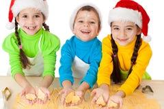 Drei lächelnde Kinder, die Teig zeigen Lizenzfreie Stockfotos