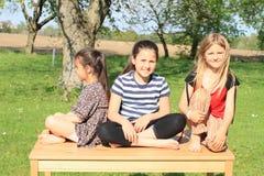 Drei lächelnde Mädchen, die auf dem Tisch sitzen Stockbild