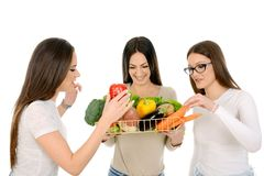 Drei lächelnde Mädchen, die Gemüse halten lizenzfreie stockfotos