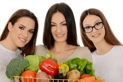 Drei lächelnde Mädchen, die Gemüse halten lizenzfreie stockbilder