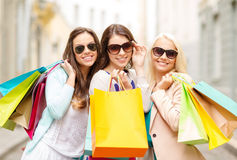 Drei lächelnde Mädchen mit Einkaufstaschen in ctiy stockfotos