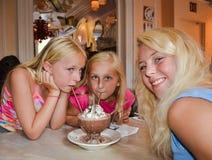 Drei lächelnde Mädchen teilen einen Nachtisch stockfotos