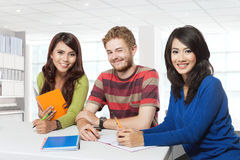 Drei lächelnde Studenten, die zusammen studieren Lizenzfreies Stockfoto