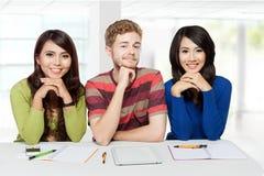 Drei lächelnde Studenten, die zusammen studieren Stockbild