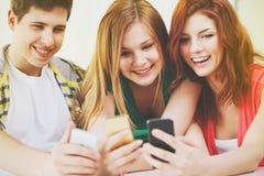 Drei lächelnde Studenten mit Smartphone in der Schule Lizenzfreie Stockfotos